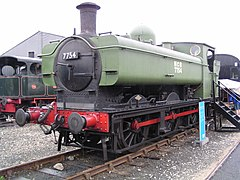 "A pannier tank locomotive is on static display with wooden steps leading up to the cab. The cab, bunker, and pannier tank are painted light green. The chimney, smokebox, splashers, running plate, and wheels are all in black. The front buffer beam and coupling rods are red. The words ""NCB 7754"" are shown in white on the side of the pannier tank. The number is also shown on the smokebox door in white letters."