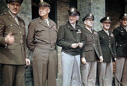 "Awards ceremony at RAF Debden, April 1944, illustrating varying shades of olive drab and the M-1944 ""Ike jacket"". Light shade 33 on left, dark shade 51 on right. Trousers are shade 33, khaki shade 1, and drab shade 54. The three combinations at right are ""pinks and greens"". Generals Anton; Eisenhower; Carl Spaatz; Jimmy Doolittle, CO 8th Air Force; Gen. William Kepner, CO, 8th AF Fighter Command, Col. Don Blakeslee.Debden April 1944.JPG"