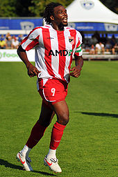 A black man with mid-length hair and a beard jogs across a grassy surface.  He is wearing a red and white striped soccer jersey, red shorts and red socks.
