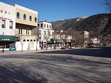 A set of attached two and three-story commercial buildings seen from across a street with a mountain behind them