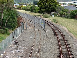 Gracefield Branch - The Hutt Workshops road enters the fenced workshops yard (left), while the branch line (right) runs along the perimeter of the workshops yard.