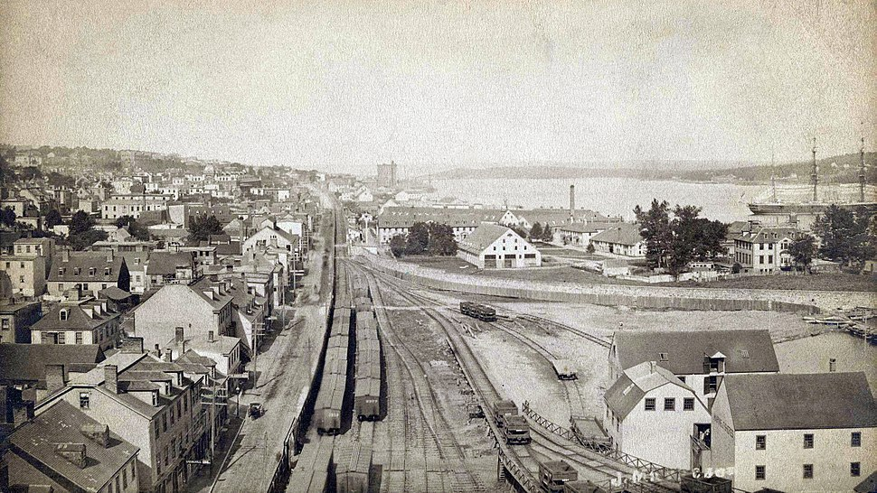 Cityscape bisected by central traintracks, with dense buildings to the left and harbourfront to the right