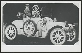 blakc and white photograph of a young man and woman in an early 20th century open-top motor-car, with young child between them.