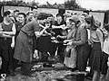Hop pickers gather around a camp fire for their evening meal on a hop farm in Yalding, Kent during 1944. D22176.jpg
