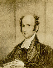 A man, bald on top with thick tufts of hair on either side of his head, wearing a black robe and white shirt