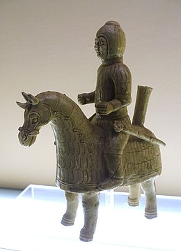 Photo of a glazed terracotta statue showing a horse and its rider, both decked in lamellar armour