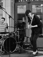 """Una banda local, Interstate Traffic, actúa fuera del Morris Performing Arts Center en el centro de South Bend como parte del festival de música """"South By South Bend"""".  En la foto aparecen dos miembros tocando una batería y una guitarra eléctrica."""