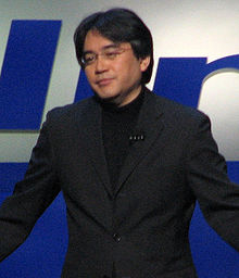 A Japanese man wearing a pair of glasses, a black suit jacket, and a black shirt, facing to the left. The man stands behind a blue and white background.