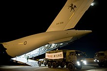 Colour photo of a truck with a sign marked with Japanese characters over its cargo compartment driving away from the rear ramp of a grey aircraft at night