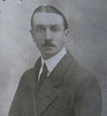 A mid-length portrait of a man of about 30 in a conservative suit and wearing a moustache, facing the camera.