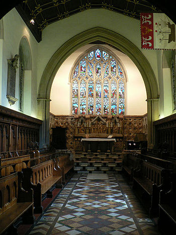 The same chapel with a wider chancel arch, decorated tiles, and a stone reredos below a large stained glass window. A flag with a ship on it hangs from high on the right wall
