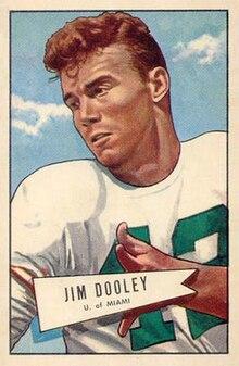 Piedpilkkartilustraĵo de Dooley portanta blankan numero 42 piedpilkĵerzon kun kusenetoj kaj neniu kasko