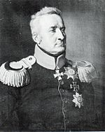 Black and white print shows a stern-looking man with short hair. He wears a dark military coat with a light-colored collar and epaulettes. An Iron Cross can be seen pinned to his coat.