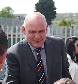 A balding man in a grey suit and a striped tie smiles as he greets Luton supporters at Kenilworth Road