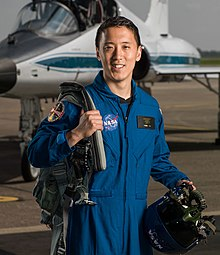An Asian man in a blue flight suit is standing in front of a jet fighter, carrying pilot's equipment, facing the camera and smiling.