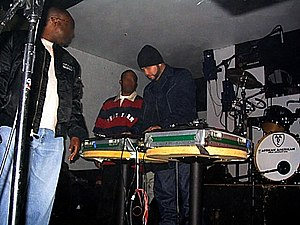 "KDAY - Former KDAY radio personality Greg Mack (far left) and ""mixmaster"" DJ Julio G (center) at the KDAY AM 1580 20th anniversary in 2003."
