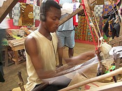 A man weaves Akan Kente cloth using a traditional loom while listening to music, Bonwire village, Ejisu-Juaben Municipal District, Ashanti Region, Ghana.