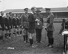 Czarno-białe zdjęcie z rugby, w którym trzej mężczyźni w mundurach wojskowych, z których jeden jest King George, przedstawić srebrny trofeum gracz rugby ubrani w czarnym zestawie.  Za w linii jest reszta zespołu.