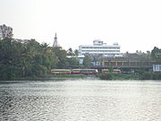 View across a lake of buses, trees and an urban skyline