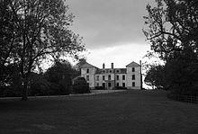 Extérieur d'une assez grande maison de campagne dans de vastes jardins