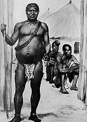 A black-and-white image depicting a middle-aged African king. Though at first glance a tall, strong-looking man, the subject's condition appears to have deteriorated with age; his belly appears severely bloated. He wears an animal-skin loincloth and a necklace made from what appear to be the teeth of various creatures. He holds a long spear in his right hand, which rests on the ground.