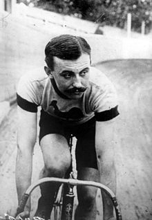 A man on a bicycle, riding on an outdoor velodrome.
