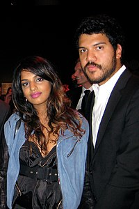 A man and a woman standing together. Both black hair and dark skin. The woman is wearing a light blue jacket over a black dress, and the man is wearing a white shirt and a black jacket.