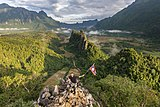 Man on a motorcycle holding a flag of Laos in front of green karst peaks at the top of Mount Nam Xay, Vang Vieng, Laos.jpg