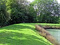 Matching Pond fishing lake embankment path at Matching, Essex, England.jpg