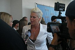 Mia Michaels dressed in a white suit with bleach blond hair standing in front of a journalist while being filmed by an unidentified cameraman.