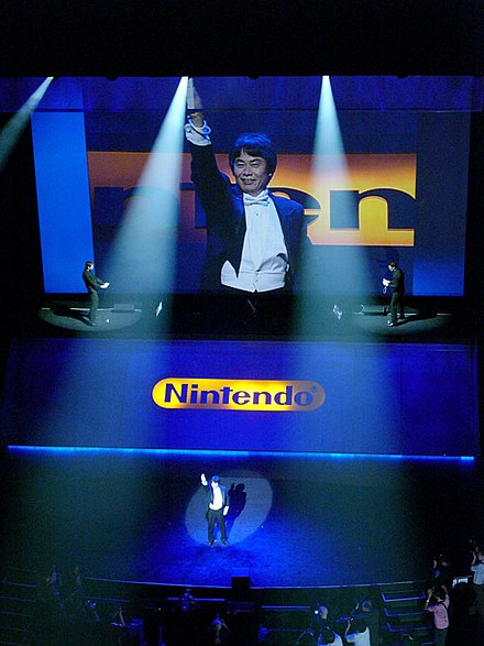 Miyamoto holding up a Wii Remote at E3 2006 Miyamoto-san conductor E3.jpg