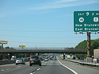 A mulitlane freeway in an urbanized area with two sets of roads in each direction. A green sign is visible in between the lanes on the right side of the road reading exit 9 2 miles Route 18 U.S. Route 1 New Brunswick East Brunswick