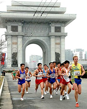 Participants in the 2012 Pyongyang Marathon running past the Arch of Triumph.jpg