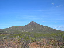 An extinct volcano with sparse greenery in the foreground