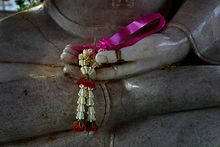 Flower offered in the hand of a Buddha image