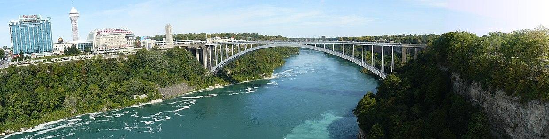 תצלום פנורמי של נהר הניאגרה וגשר הריינבו ליד מפלי הניאגרה. בצד ימין: ארצות-הברית. בצד שמאל: קנדה (לצפייה הזיזו עם העכבר את סרגל הגלילה בתחתית התמונה)