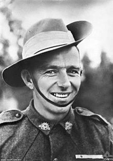 A head and shoulders portrait of a smiling man in military uniform.