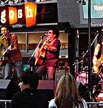 Band performing at a shopfront. Male at left is playing a guitar and is at a microphone. A fifty-something male in middle is shown partly in left profile. He has dark hair, wears sunglasses and is playing a guitar while at a microphone. A drum kit is to his left with a third band member obscured by frame cut-off. Two audience members are seen in the foreground.