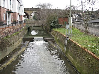 Brent Cross - The River Brent at Brent Cross. The Ordnance Survey 1:50,000 scale mapping shows a sea of dark green here as the A406 North Circular Road and the A41 Hendon Way meet at the Brent Cross Flyover. A small weir impounds a head of water as the river flows down towards the Brent Reservoir.