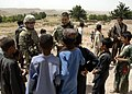 SGT Sean Bergstrom, of B Co, 3-4 Infantry and Italian Army Col Marco Cenni, talk with local boys during a visit to Ammon Khal 2011-06.jpg
