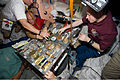 STS-129 crew members gather for a meal at the galley in the Unity node of the International Space Station.jpg