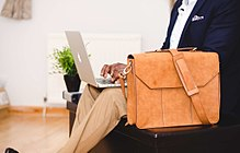 Light-brown leather bag next to man typing on laptop