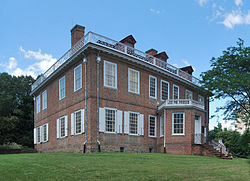 A two-story brick house with white window shutters, a wooden balustrade on top and an octagonal projecting front entrance pavilion, seen looking slightly upslope towards its right corner