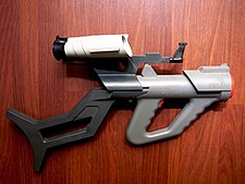 Plastic, gray toy gun with orange highlights and attached black shoulder stock and white scopes