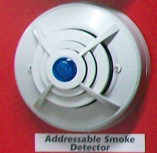 Smoke detector device that detects smoke, typically as an indicator of fire