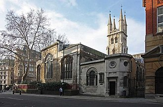 À la droite de la photo apparaît la façade d'un immeuble. La face avant comprend plusieurs fenêtres en ogive. Un arbre est à la gauche de l'église. À l'arrière de celle-ci, une tour de style gothique la surplombe.