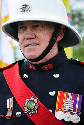 Stafford knot - A Staffordshire Fire and Rescue Service firefighter in ceremonial dress, with Stafford knots on his helmet, collars, buttons and sash