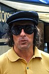 Jackie Stewart wearing a yellow T-shirt, a black cap and sunglasses