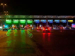 Great Belt Fixed Link - The Toll area at night. Each booth can be used for electronic toll collection (green booths), credit card (blue booths) or manual payment (yellow booths), depending on the load on each payment method.