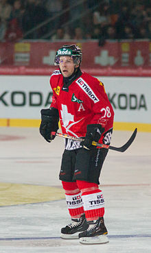 A Caucasian male ice hockey player shown skating on ice in a full-body shot. He is wearing a red and white sweater with a dark helmet.